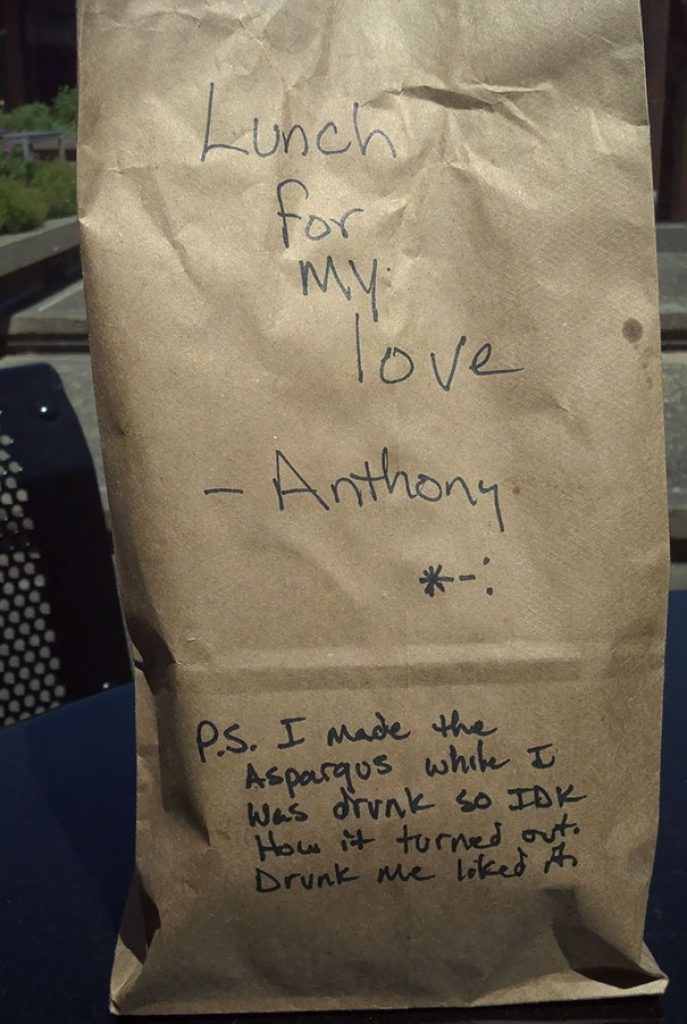 A lunch packed in a brown bag with a note