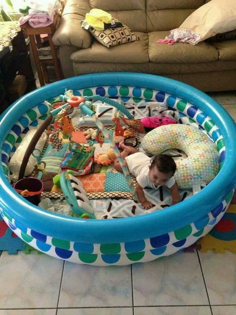 Toddler in a kiddie pool with his toys