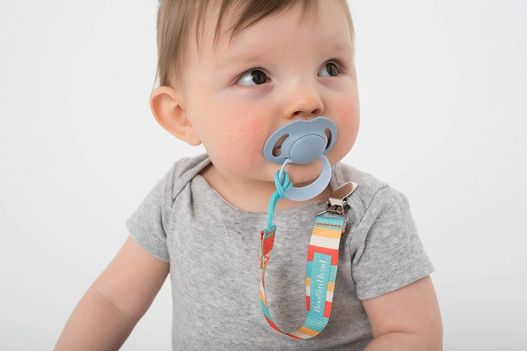 Baby with pacifier clipped to his shirt