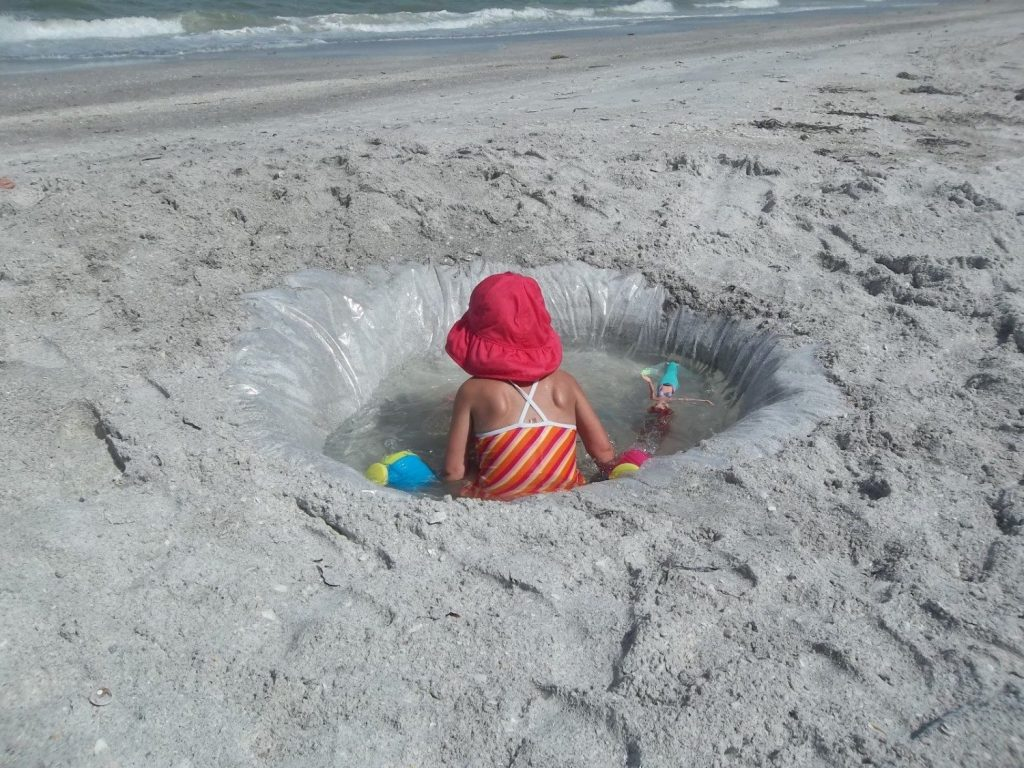 Makeshift pool at the beach with a shower curtain liner