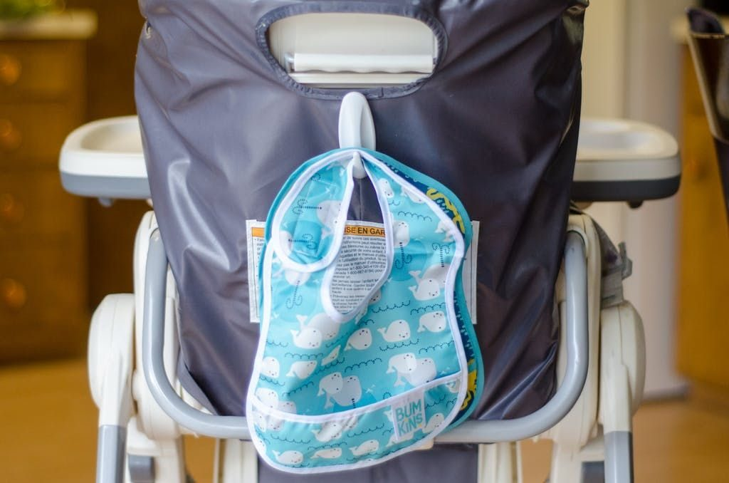 Hang a hook on the back of the highchair for bibs