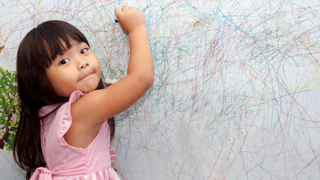 girl drawing on the walls with crayon
