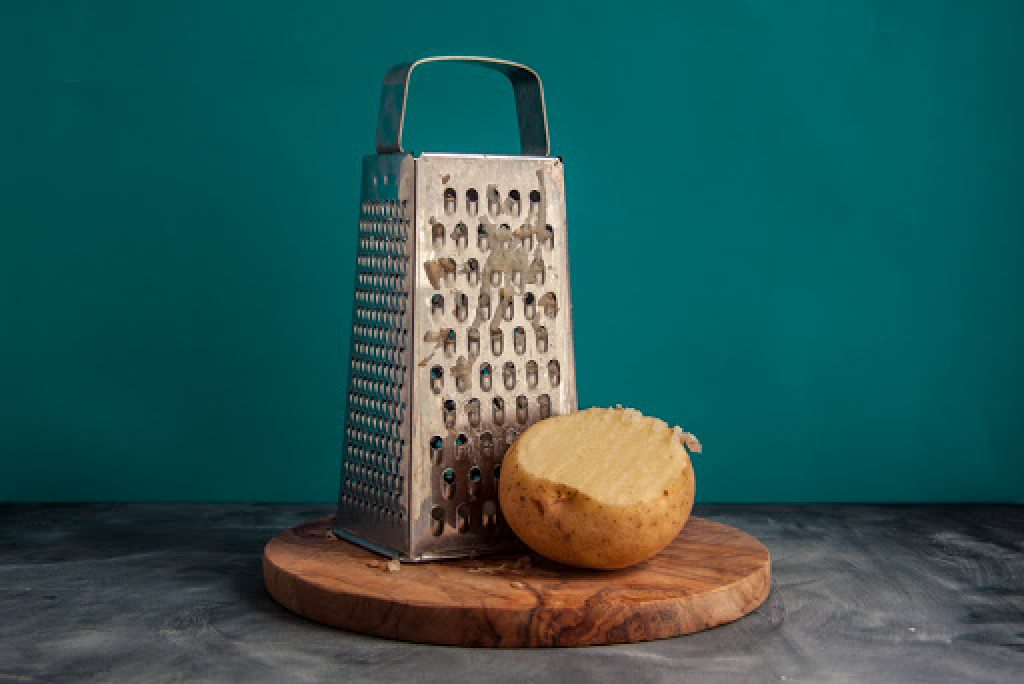 cheese grater and a potato