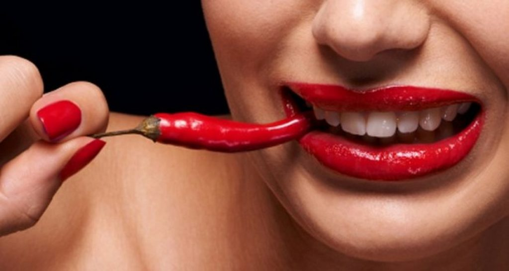 Woman eating a chili pepper